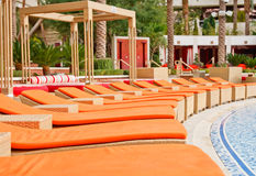Orange Chaise Lounges at a Resort Patio. A luxury resort patio around a pool with orange chaise lounges stock photos