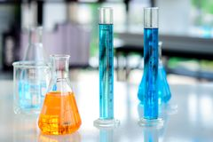 Orange Chemikalien in der Flasche und blaue Chemikalien in den Zylinderrohren auf dem Tisch gesetzt lizenzfreies stockbild