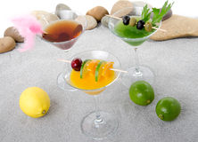 Orange, cherry and cucumber cocktails in a environment of sand a Stock Photo