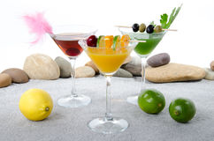 Orange, cherry and cucumber cocktails in a environment of sand a Royalty Free Stock Photos