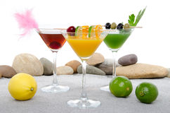 Orange, cherry and cucumber cocktails in a environment of sand a Stock Image