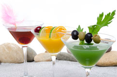 Orange, cherry and green vegetables cocktails on a beach environ Royalty Free Stock Photos