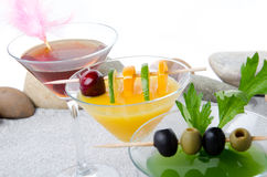 Orange, cherry and green vegetables cocktails on a beach environ Royalty Free Stock Image