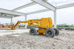 Orange cherry picker. Boom lift. Cherry picker is parked below concrete skeleton of new assembled building frame stock photos