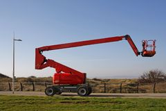 Orange cherry picker. Side view against a blue sky stock images
