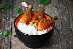 Orange chicken thighs with rice in bowl. Asian cuisine: sweet and spicy orange chicken thighs with steamed rice Royalty Free Stock Images