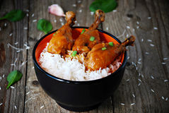 Orange chicken thighs with white rice in bowl. Asian cuisine: sticky orange chicken thighs with white jasmine rice in bowl on rustic wooden table, garnished with Stock Images