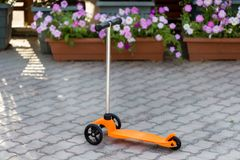 An orange children`s scooter stands on the road. Summer, rest, sport. An orange children`s scooter stands on the road. Summer, rest royalty free stock photo