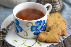 Orange Chocolate Chip Shortbread Cookies Tea Cup and Saucer. Heart shaped orange chocolate chip cookies on edge of flowered tea saucer with blue flowered tea cup Royalty Free Stock Photos