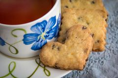 Orange Chocolate Chip Shortbread Cookies on Tea Saucer. Heart shaped orange chocolate chip cookies on edge of flowered tea saucer Royalty Free Stock Image