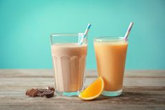 Orange and chocolate milkshakes in glasses royalty free stock photography