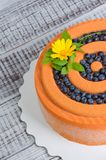 Orange chocolate velour cake with flowers, blueberries and basil. An orange chocolate velour cake with flowers, blueberries and basil Royalty Free Stock Images
