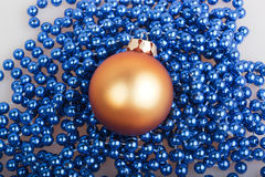 Orange Christmas ball and blue beads Stock Photos