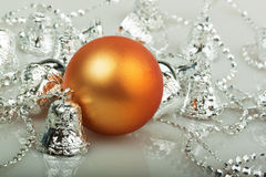 Orange Christmas ball with silver bells. On white Royalty Free Stock Image