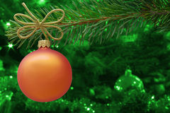 Christmas card concept. Orange Christmas bauble and a spruce branch with copy space. Royalty Free Stock Photo