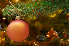Christmas card concept. Orange Christmas bauble and spruce branch with copy space. Stock Photos