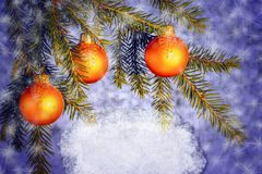 Orange Christmas ornaments on spruce branches on a blue shiny background with snowflakes. Place for the text. Blank for royalty free stock photos