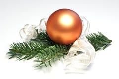 Orange christmas tree ball. And fir twig Royalty Free Stock Photography