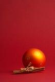 Orange christmas tree ball - orange Weihnachtskugel. Orange Christmas Tree Ball with Cinnamon on red Background - orange Weihnachtskugel mit Zimtstangen vor stock photography