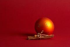 Orange christmas tree ball - orange Weihnachtskugel. Orange Christmas Tree Ball with Cinnamon on red Background - orange Weihnachtskugel mit Zimtstangen vor stock photos