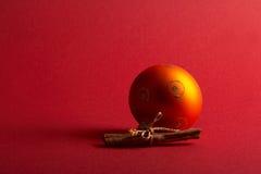 Orange christmas tree ball - orange Weihnachtskugel. Orange Christmas Tree Ball with Cinnamon on red Background - orange Weihnachtskugel mit Zimtstangen vor royalty free stock photo