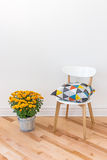 Orange chrysanthemums bright cushion on a chair. Bright cushion on a chair, and orange chrysanthemums decorating a room royalty free stock photo