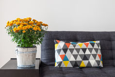 Orange chrysanthemums and bright cushion on a sofa. Bright cushion on a sofa, and orange chrysanthemums on a side table stock photo