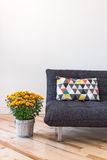 Orange chrysanthemums and sofa with bright cushion Royalty Free Stock Photography