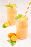 Orange citrus kumquat  fruit smoothie in glass jars with straw, mint leaf, cute ripe berry, vertical, close up. Stock Photo