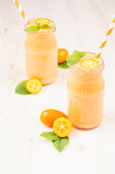 Orange citrus kumquat fruit smoothie in glass jars with straw, mint leaf, cute ripe berry, vertical, close up. Royalty Free Stock Photography