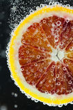 Orange citrus slice falling into water Stock Images