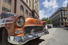 Orange classic car in Old Havana, Cuba. Orange classic car in front of the Bacardi building in Old Havana, Cuba royalty free stock photography