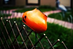 Orange clay pot on a wattled fence in a garden. stock photo