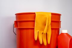 Orange cleaning supplies against a clean background for copy-space royalty free stock photos