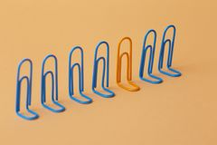Orange clip among the blues, unlikeness to others, the concept of individuality, optimism, creative idea with office paper clips,. Concept of psychology stock image
