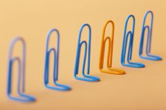 Orange clip among the blues, unlikeness to others, the concept of individuality, optimism, creative idea with office paper clips,. Concept of psychology royalty free stock image