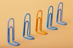 Orange clip among the blues, unlikeness to others, the concept of individuality, optimism, creative idea with office paper clips, royalty free stock images