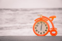 Orange clock on sand. At the sunset beach, Relax concept Royalty Free Stock Image