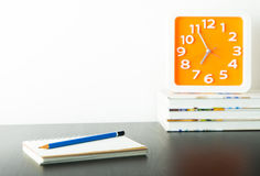 Orange clock on stacked book with white copy space. Wall for writter Stock Image