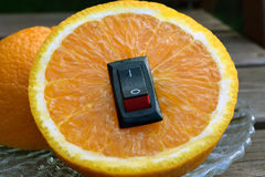 Orange close up with with inserted power switch. Royalty Free Stock Image
