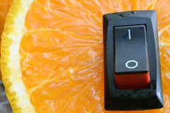 Orange close up with with inserted power switch. Royalty Free Stock Photos