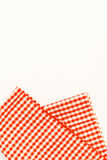 Orange cloth, a kitchen towel with a checkered pattern, on a whi. Te background Royalty Free Stock Photos