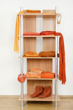 Orange clothes nicely arranged on a shelf. Stock Images