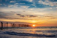 Orange cloud on sea horizon with leading iron poles. Towards the sun royalty free stock image