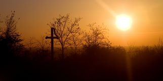 An orange cloudless sunset with silhouette of a cross in the foreground stock photo