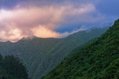 Orange clouds in the blue sky over forested mountains. Madeira, Portugal. Orange clouds in the blue sky over forested mountains. View from Balcoes viewpoint in stock image