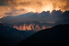 Orange clouds in dolomite mountains. Dramatic light and clouds in the dolomite mountains in Italy Stock Photography