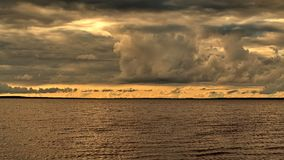 Sunset and storm clouds over lake Royalty Free Stock Photos