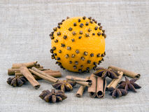 Orange with cloves on linen background Stock Images