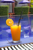 Orange cocktail. Stands on edge of pool Royalty Free Stock Photography
